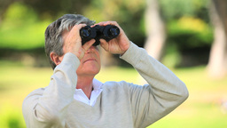 Mature man watching something through binoculars Footage