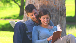 Young couple reading books under a tree Footage