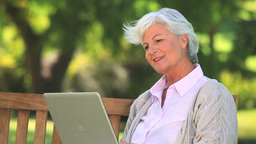 Mature woman chatting on her laptop Live Action