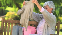 Mature woman on a park bench with her shopping Live Action