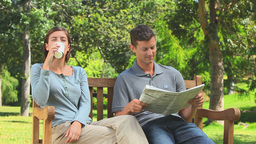 Young couple reading a newspaper outdoors Footage