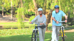 Mature couple walking with their bikes Footage