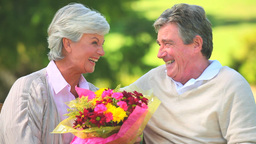 Elderly couple holding a bunch of flowers while si Footage