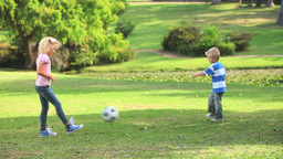 Young boy and his sister playing together with a b Footage