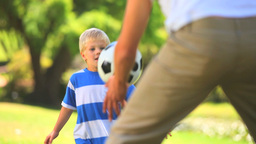 Young boy and his father playing with a ball Footage
