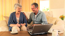 Retired couple happy at having used their laptop s Footage
