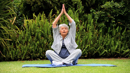 Greyhaired Woman Practising Oriental Exercises In  stock footage