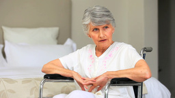 Elderly greyhaired woman thinking in a wheelchair Footage