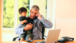 Man doing office work while holding baby Footage