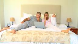 Couple on bed enjoying something hilarious on lapt Footage