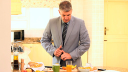 Man on phone rushing to eat breakfast and get off  Footage