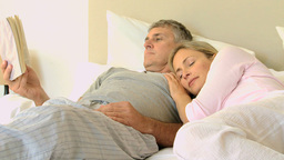 Man reading a book in bed while his wife sleeps on Footage
