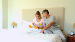 Young woman enjoying breakfast in bed brought by h Footage