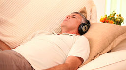 Man lying on sofa listening to music with headphones Footage