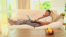 Man lying on sofa excited about something on lapto Footage