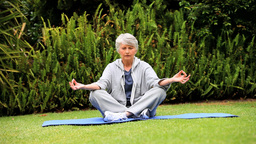 Greyhaired woman doing yoga in the garden Footage