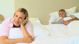 Blonde woman posing on a bed while husband reads a Footage