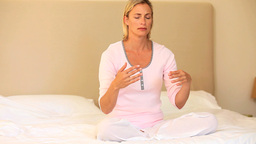 Young woman doing mediation sitting on bed Footage