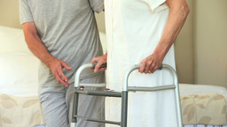 Male nurse helping woman to walk with a zimmer fra Footage