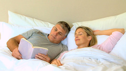 Man reading a book in bed with wife Footage