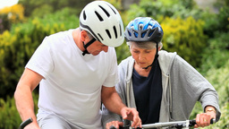 Mature couple riding bicycles outside Footage