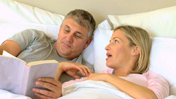 Couple reading a book in bed Footage
