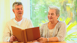 Mature Couple Looking At An Album stock footage
