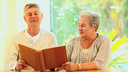 Retired couple looking at an album Footage