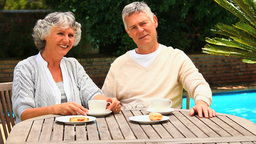 Mature Couple Having A Snack By A Swimming Pool stock footage