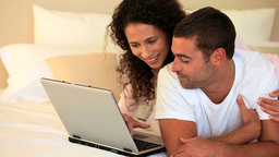 Young couple laughing at something on their laptop Footage
