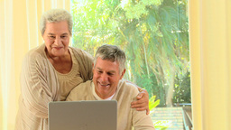 Elderly couple laughing at something on a laptop Footage
