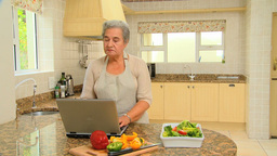Elderly woman looking up a recipe on a laptop Footage