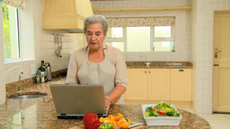 Retired woman looking up a recipe on her laptop Footage