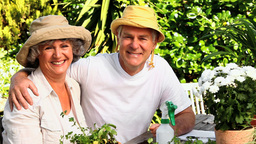 Mature couple wearing sunhats posing outdoors for  Footage