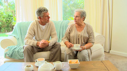 Mature couple sitting drinking tea and chatting Footage