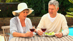 Mature couple clinking their glasses of red wine in garden Live Action
