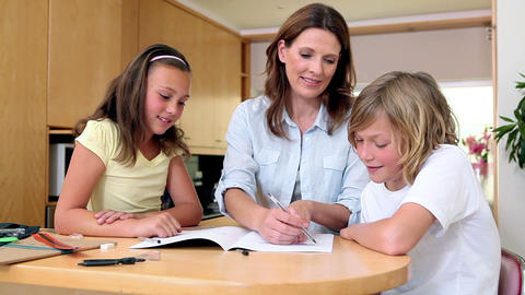 Mother helping her children with homework Footage