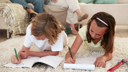 Siblings doing their homework on the living room floor with their parents behind Footage