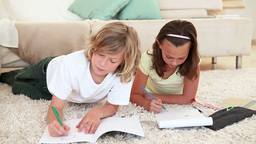 Brother and sister doing homework on the living room floor Footage