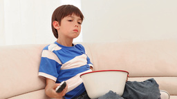 Boy eating popcorn while he watches television Footage