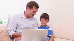 Father and son with laptop in the living room Footage