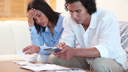 Frustrated couple calculating their expenses Footage
