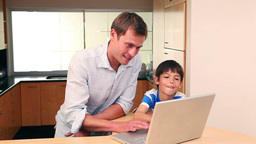 Father and son with laptop in the kitchen Live Action