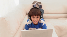 Boy using a laptop is wearing headphone Footage
