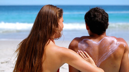 Woman applying sunscreen on her boyfriend Live Action