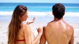 Brunette applying sunscreen on her boyfriend Footage