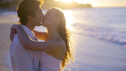 Couple kissing on the beach during the sunset Footage