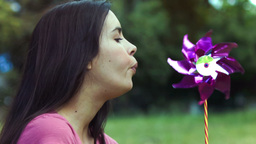 Woman breathing on a pinwheel in slow motion Live Action