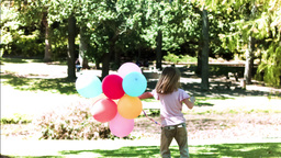 Child holding balloons in slow motion Footage