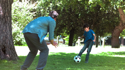 Boy playing soccer in slow motion with his father Footage